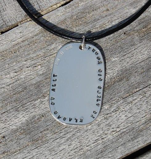 ovalt silversmycke med text på trä utomhus