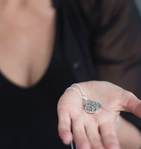 droppformat silversmycke med kvinnoansikte i handflata på en kvinna som man ser i bakgrunden