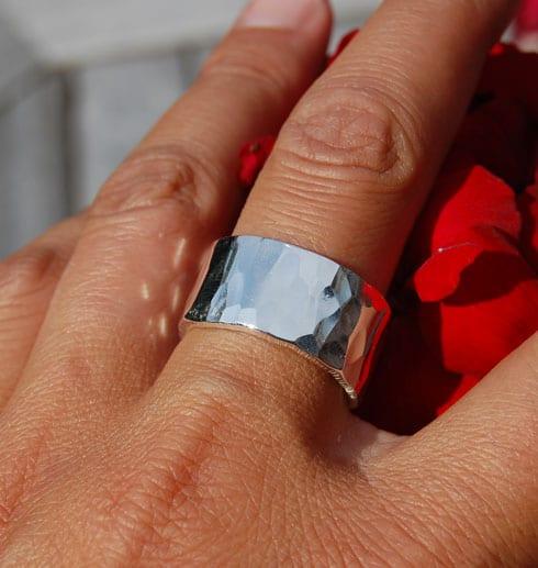bred hamrad silverring på finger utomhus