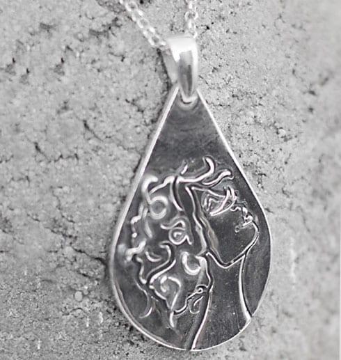 droppformat silversmycke med kvinnoansikte på går betong