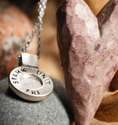 runt silversmycke i kedja med texten STARK, UNIK, FRI på sten med rosa hjärta bredvid