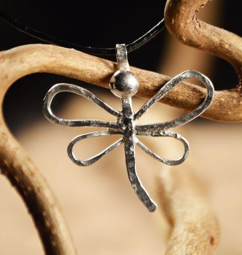 trollslända i silver mot trädgren