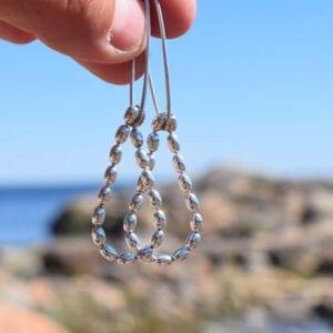 droppfromade silverörhängen som hålls i en fingernypa ute vid havet
