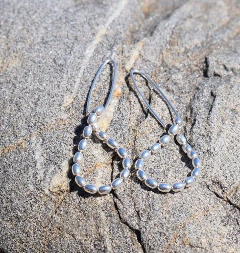 droppformade silverörhängen på klippa utomhus