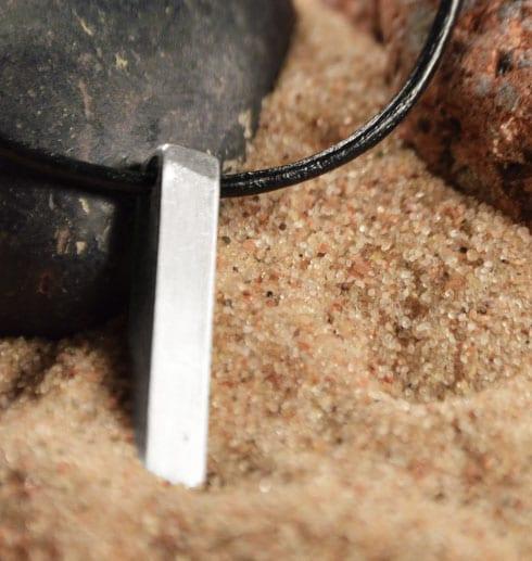 silverstav i läderrem i sand