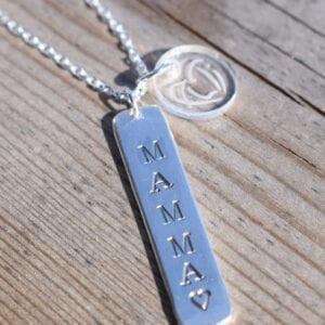 silversmycke med texten MAMMA på trä utomhus