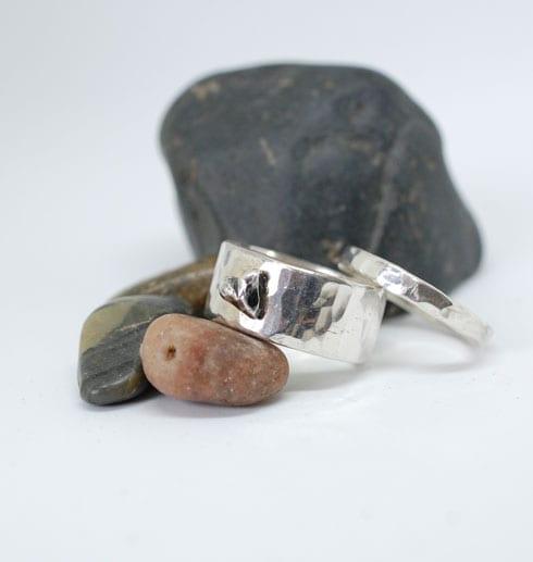 två silverringar med vit bakgrund och stenar