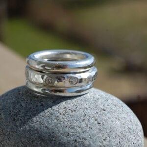 tre grova silverringar på grå sten utomhus