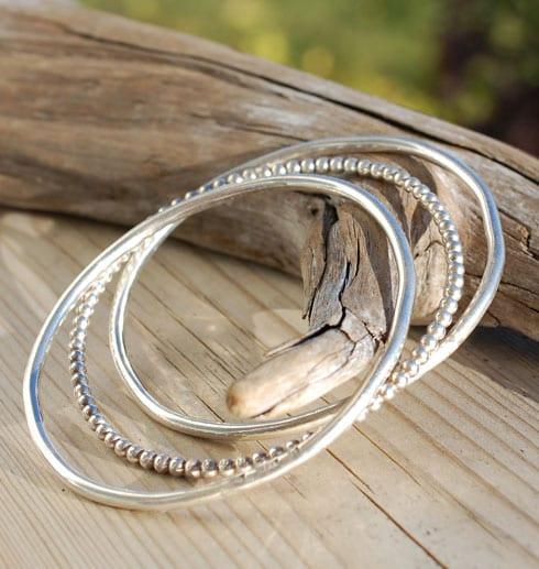 tre silverarmband på trä mot trädgren utomhus