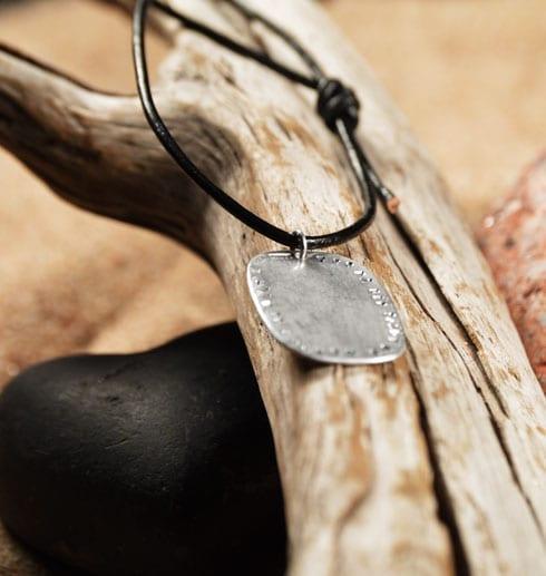 silversmycke i läderrem på trägren med sand och sten bakom
