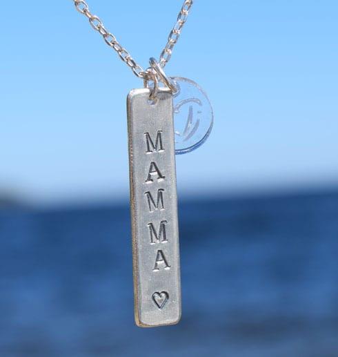silversmycke med texten MAMMA hängande utomhus vid havet