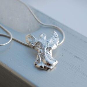 ängel i silver på metallräcke utomhus
