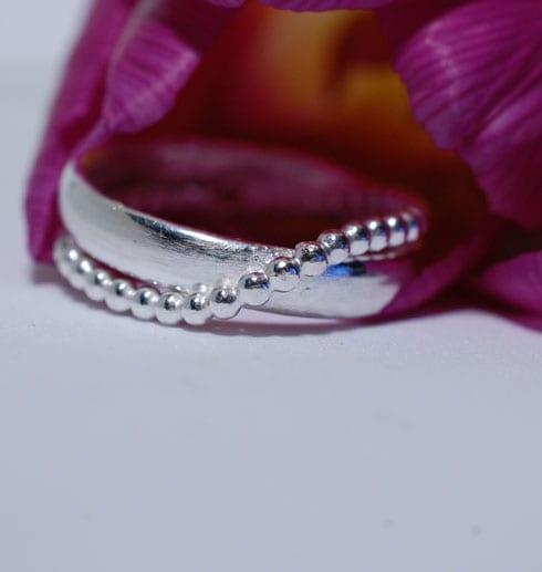 silverring med lila tuplan bakom
