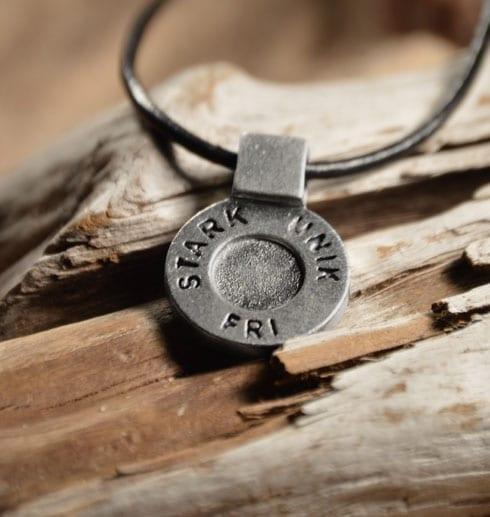 runt silversmycke i läderrem med texten STARK, UNIK, FRI på trä