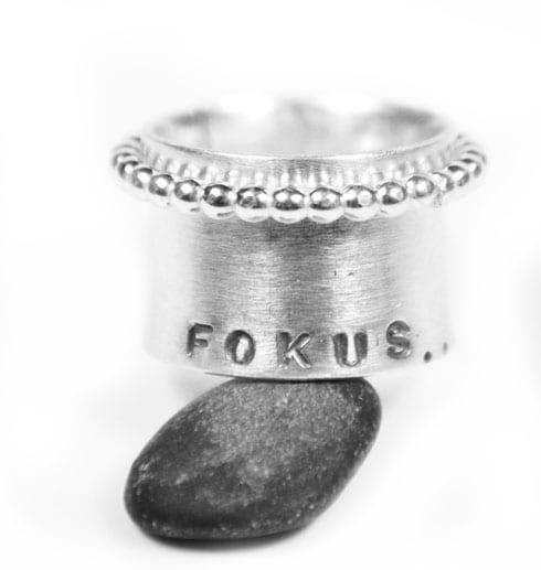 bred silverring med texten FOKUS på grå sten med vit bakgrund