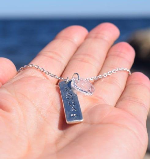 silversmycke med texten MAMMA liggande i handflata utomhus vid havet