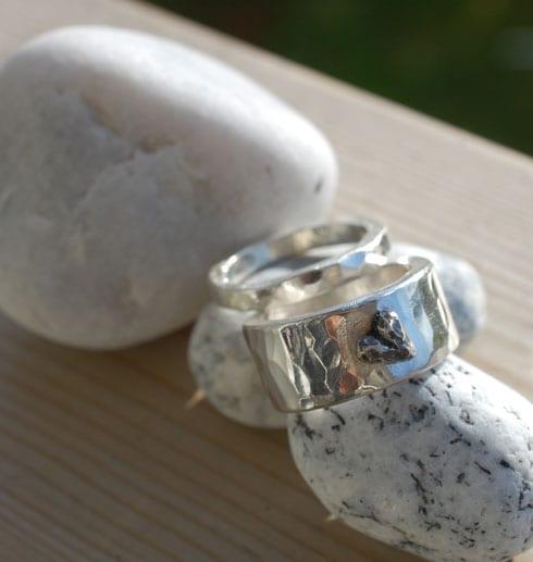 två silverringar på stenar utomhus