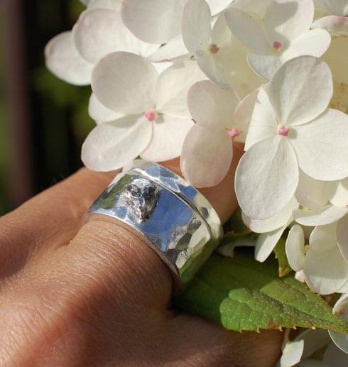 silverringar med hjärta på finger med vit blomma utomhus