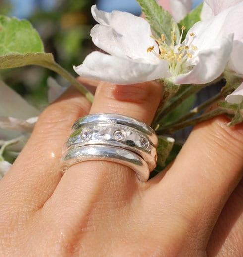 tre grova silverringar på finger med äppelblomma utomhus