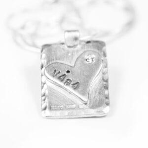 silversmycke med hjärta och text på vit bakgrund