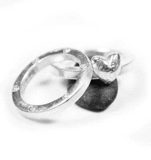 två silverringar med hjärta på sten med vit bakgrund