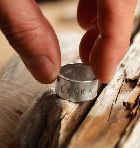 fingrar som lägger ner en silverring med text på träbit