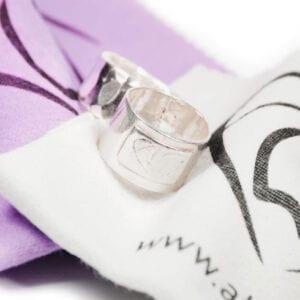silverring på lila och grå putsduk