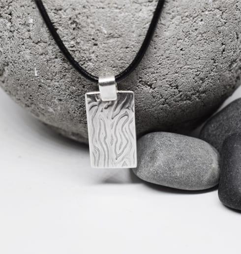 silverplatta med mönster i läderrem mot stenar och betong