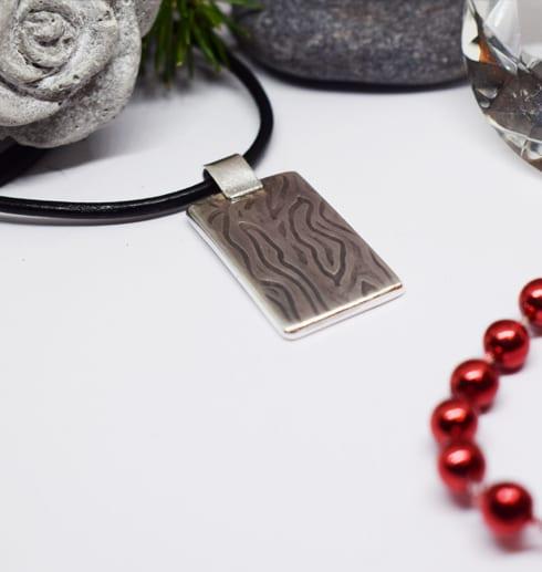 silverplatta med mönster i läderrem med stenar och röda kulor