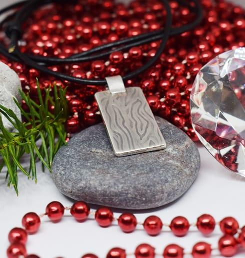 silverhalsband med mönster i läderrem med röda kulor