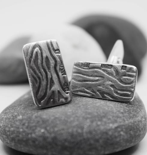 manchettknappar i silver med mönster på stenar