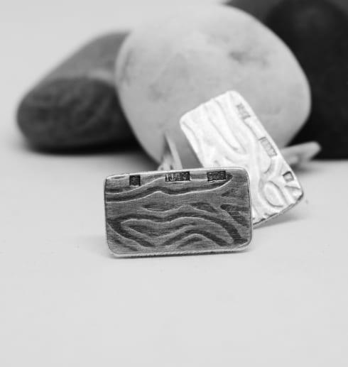 manchettknappar i silver med mönster med stenar bakom