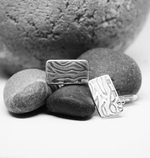 mönstrade manchettknappar på grå stenar