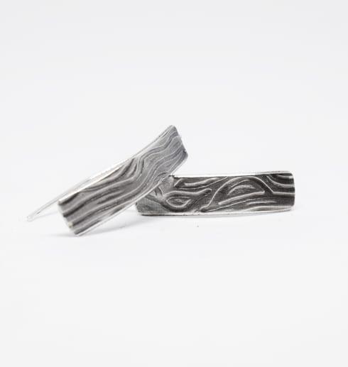 silverörhängen med mönster mot vit bakgrund