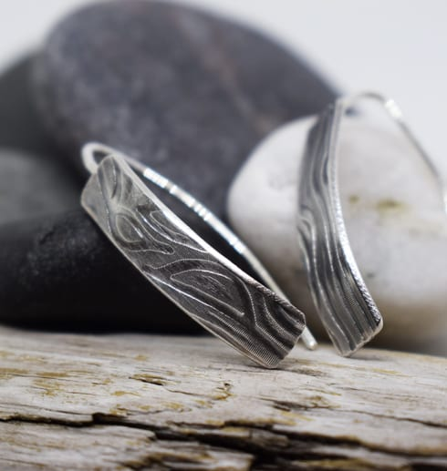 mönstrade silverörhängen på trä med stenar