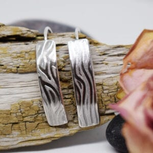 silverörhängen med mösnter på träbit med blomma bredvid