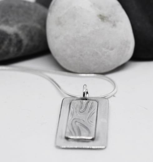 silverhalsband på vit botten med stenar bakom