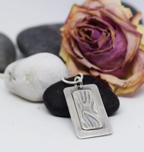 silverhalsband mot stenar med ros bakom