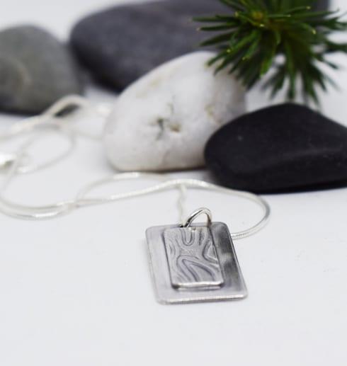 silverhalsband med mönster med stenar och grankvist bakom