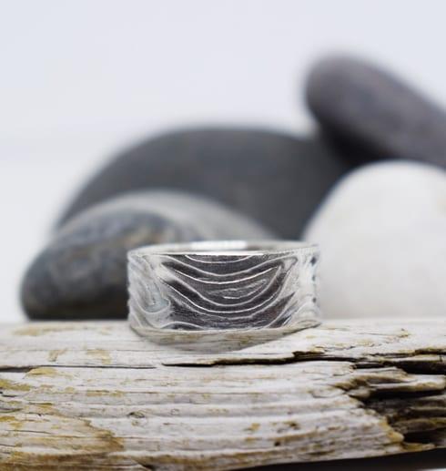 möstrad silverring på träbit med stenar bakom