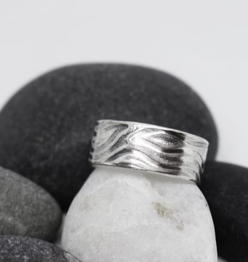 mönstrad silverring mot stenar