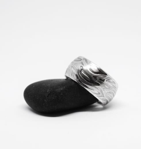 silverring med mösnter på svart sten med vit bakgrund
