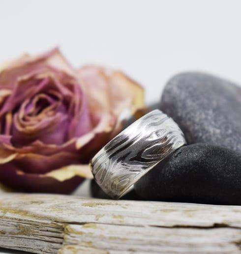 välvd mönstrad ring med ros, stenar och träbit