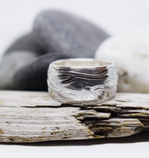 mönstrad ring med träbit och stenar bakom