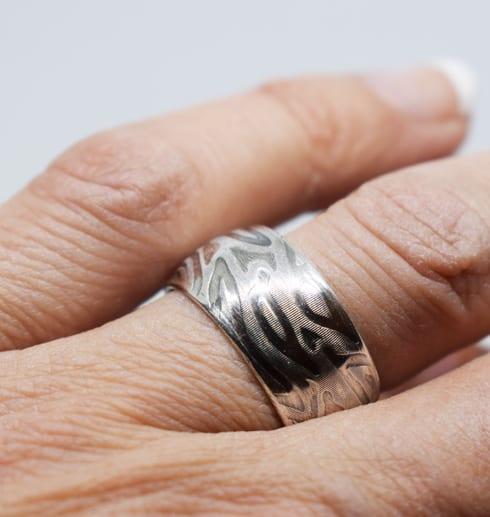mönstrad välvd silverring på finger