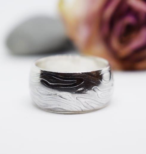 mönstrad ring på vit botten med ros och sten bakom