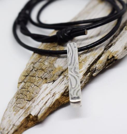 silverstav med mösnter i läderrem på träbit