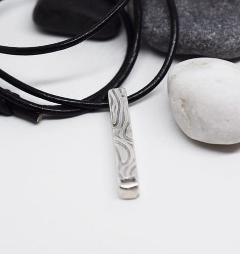 stav med mönster i silver i läderrem med stenar bakom