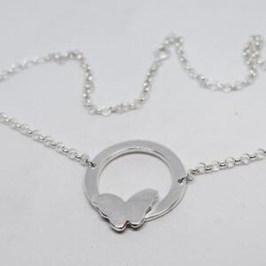 silverhalsband med fjäril på vit botten