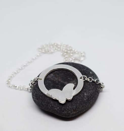 silverhalsband med fjäril på mörkgrå sten